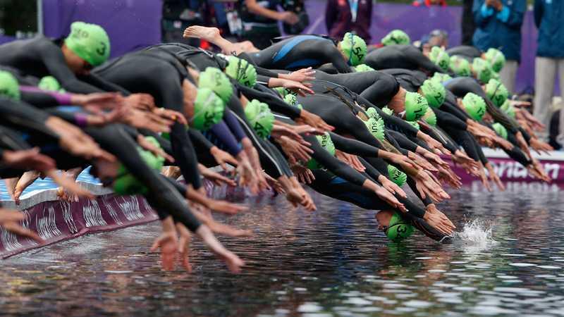 De tävlande i Triathlon dyker i vattnet.
