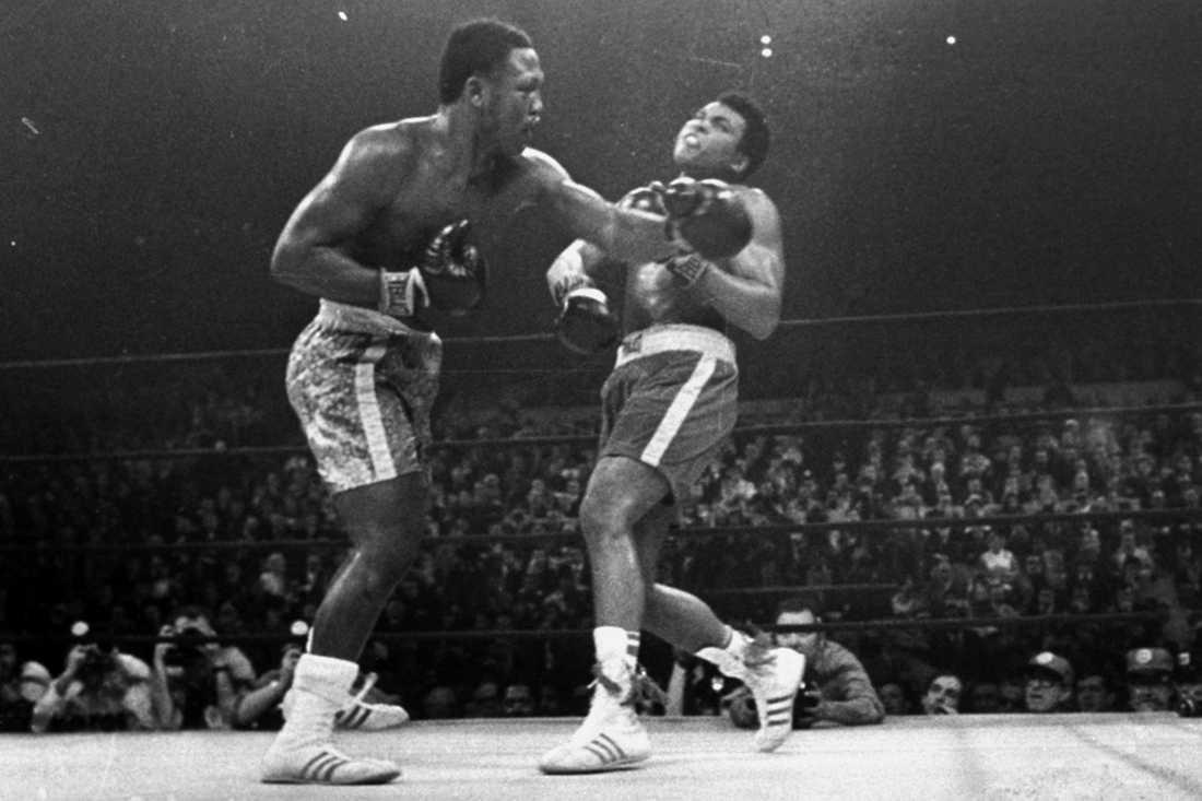 """Joe Frazier (1944-) träffar Muhammad Ali med en vänster i den berömda titelmatchen i Madison Square Garden 8 mars 1971. """"Smokin' Joe"""" vann matchen över 15 ronder och skulle sedan möta Ali två gånger till under sin karriär, bland annat i klassikern """"Thrilla in Manila"""" 1975."""