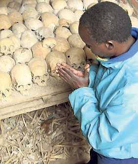 En överlevande ber vid en massgrav i Rwanda.
