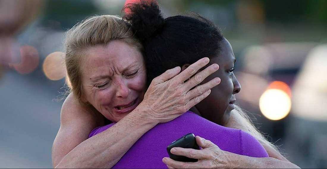 TRÖSTLÖSA  Två kvinnor som förlorat närstående omfamnar varandra utanför den biograf där James Holmes sköt ihjäl tolv personer.
