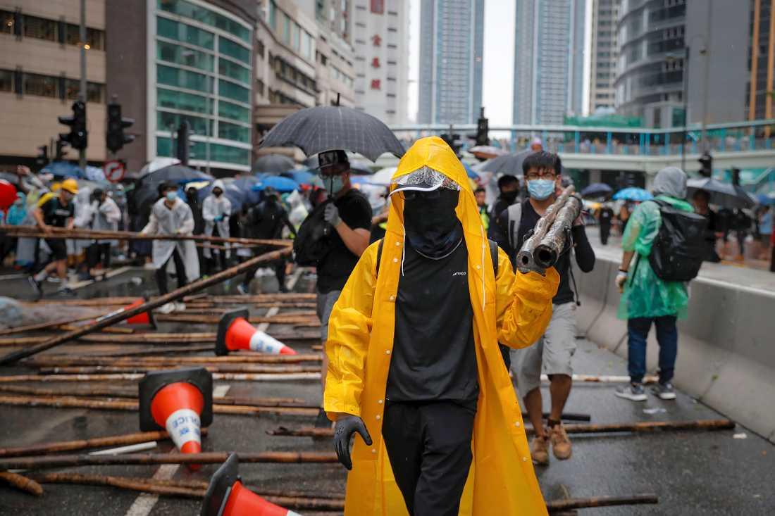 Demonstrerande använder bambupinnar för att blockera en väg under söndagens protester.