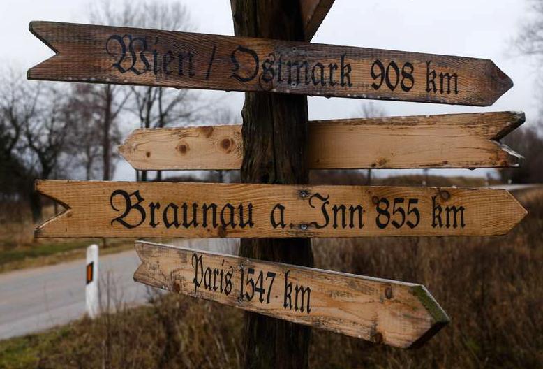 En handgjord skylt i trä står vid vägen i staden Jamel, 260 kilometer nordväst om Berlin. Skylten visar vägen till Wien, Paris och Braunau am Inn – Adolf Hitlers födelseplats.