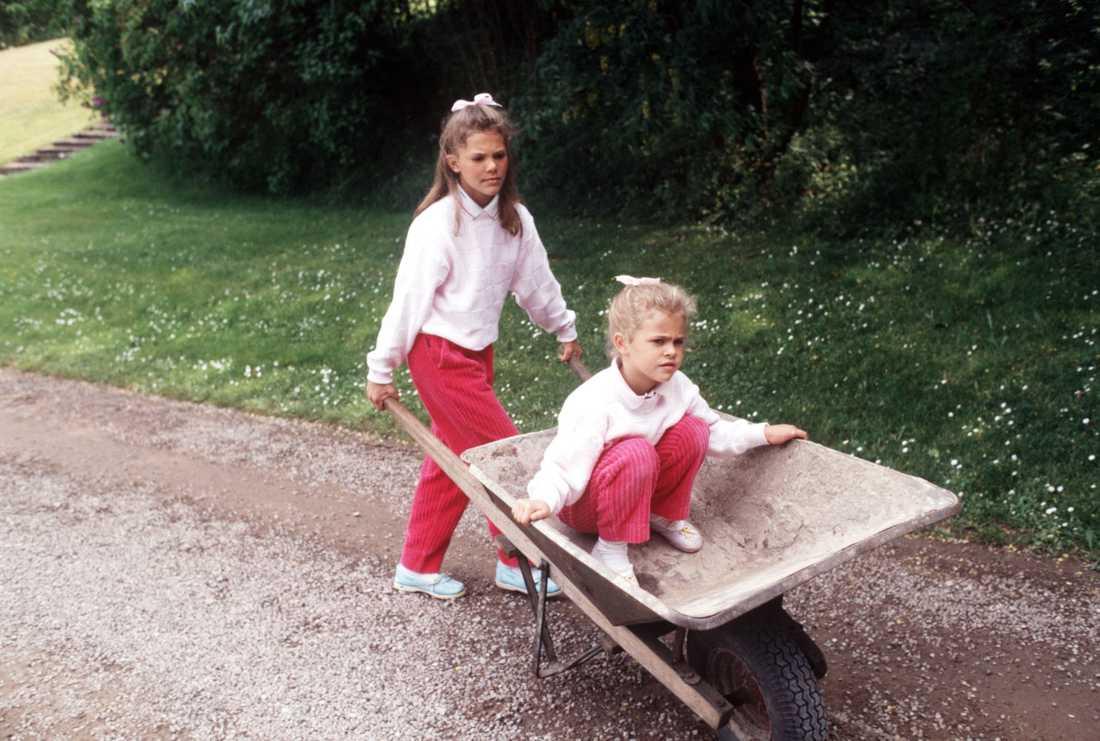 Syster kör Kungafamiljen har som synes tillbringat många och långa somrar på Solliden, det är ett av deras favoritställen. Här, sommaren 1988, kör kronprinsessan Victoria (då 11 år) sin lillasyster prinsessan Madeleine (6 år) i en skottkärra.