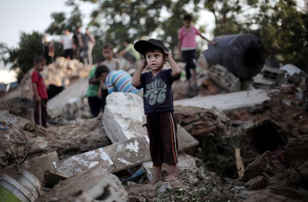 En palestinsk pojke står i resterna av ett hus som har träffats av israeliska raketer i staden Beit Hanoun den 9 juli. Den israeliska offensiven forsätter.