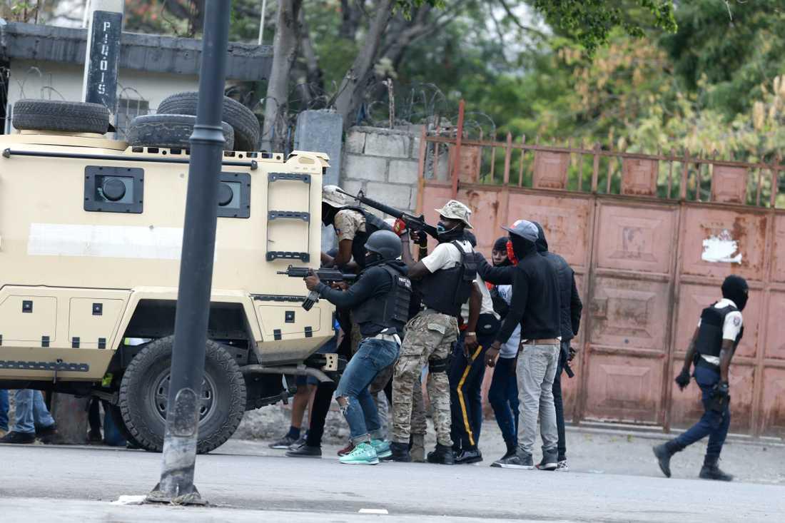 Poliser tar skydd bakom ett förstärkt fordon under skottväxling med arméns soldater, mitt i Port-au-Prince.