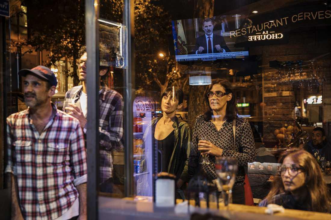Barcelonabor ser kungens tal från en bar.