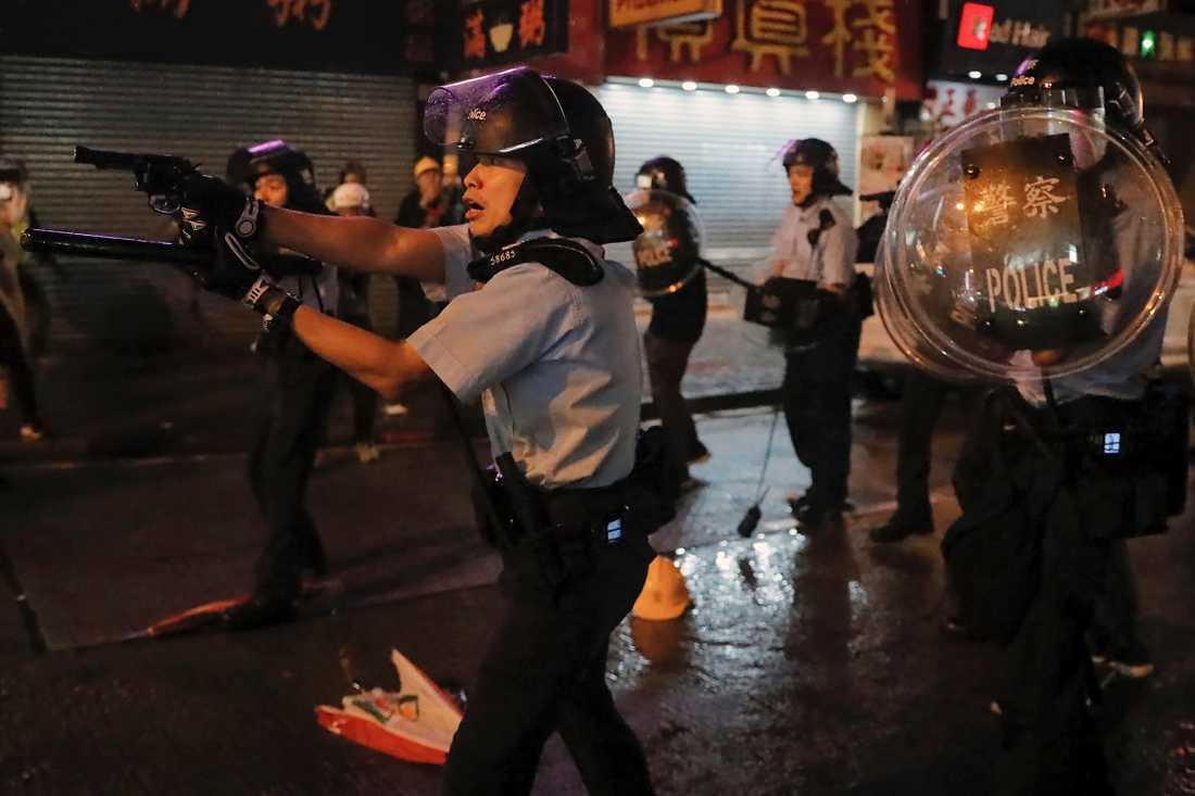 Flera poliser drog sina vapen under protesterna i Hongkong på söndagen. Minst ett skott har avlossats, enligt polisen.