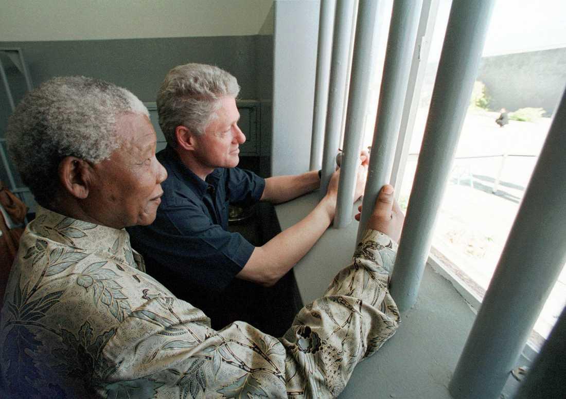 President Nelson Mandela och President Bill Clinton tittar ut från Section B, fängelsecell No. 5 på Robben Island. Mandela tillbringande aron av sina 27 fängelseår på Robben Island.
