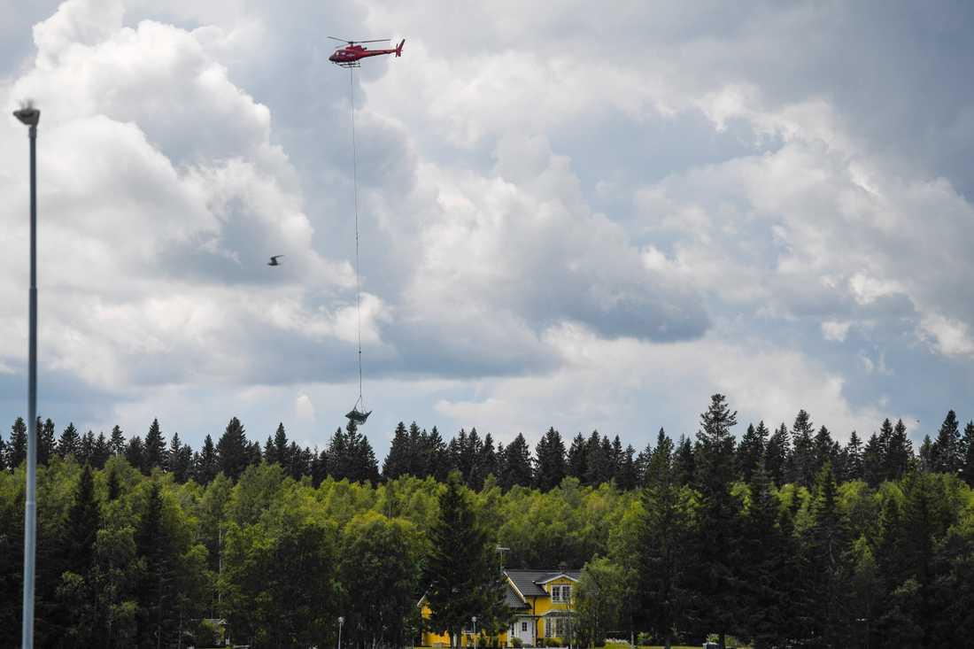 En helikopter bärgar vrakdelar från flygplanet i den flygolycka där nio personer omkom i söndags.