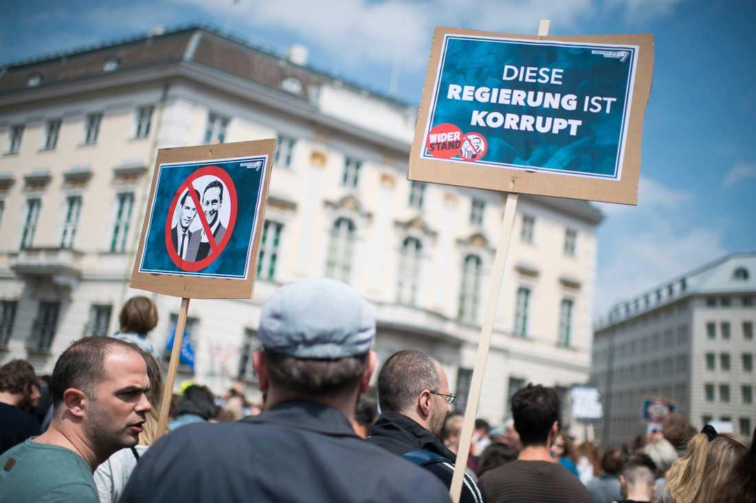 """Demonstranter samlades framför förbundskanslerns kansli i Wien i Österrike efter avslöjandet av den så kallade Ibiza-affären. På skylten till höger står """"Den här regeringen är korrupt"""". Arkivbild."""