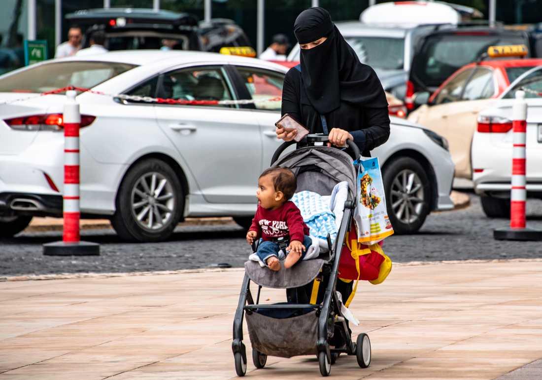 En kvinna med barnvagn.