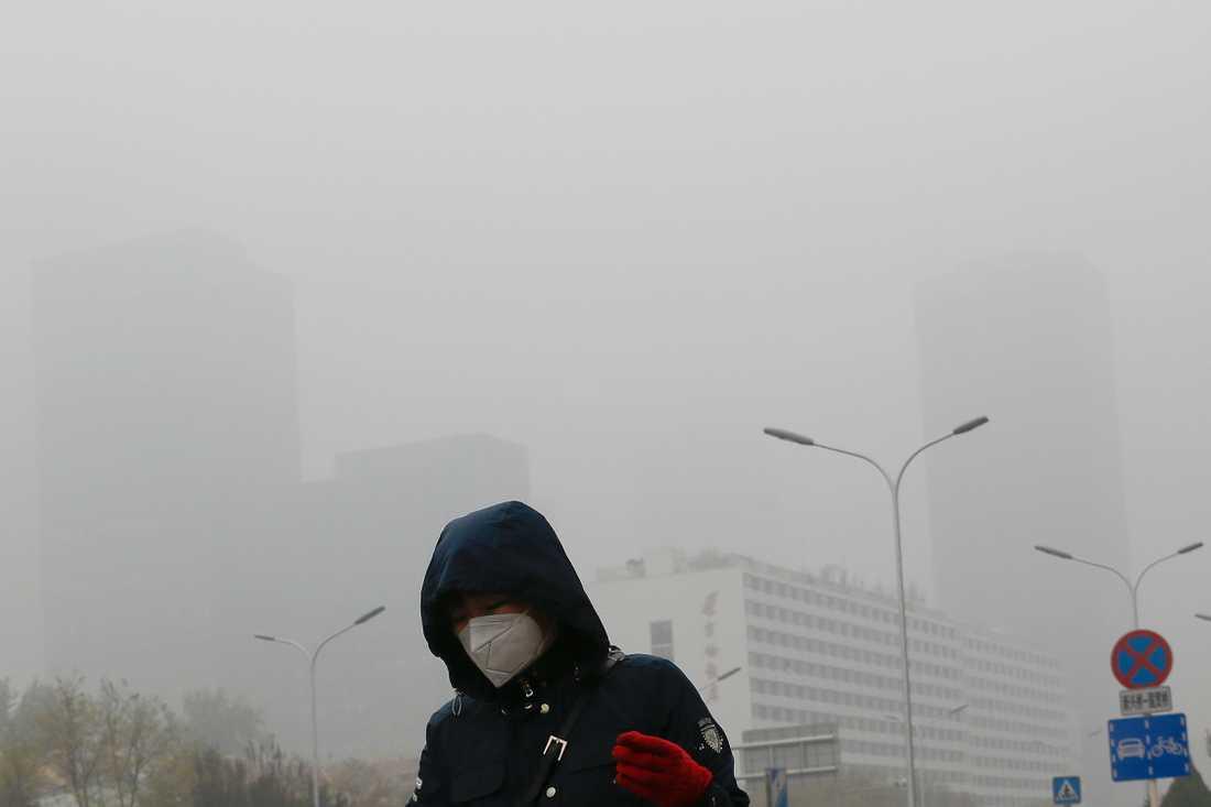 Tiotusentals människor beräknas ha dött i år till följd av luftföroreningar i Peking och Shanghai. På bilden bär en kvinna ett andningsskydd i ett smogtätt Peking. Arkivbild från 2018.