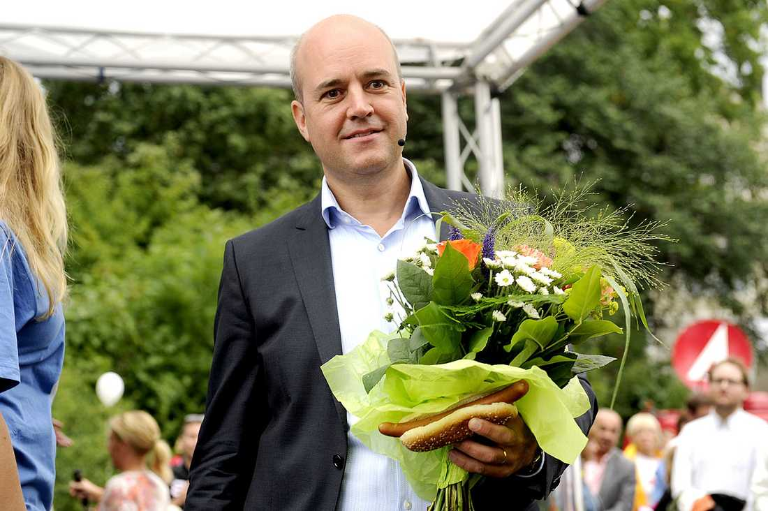 Fredrik Reinfeldt med blomsterbukett och en korv med bröd.