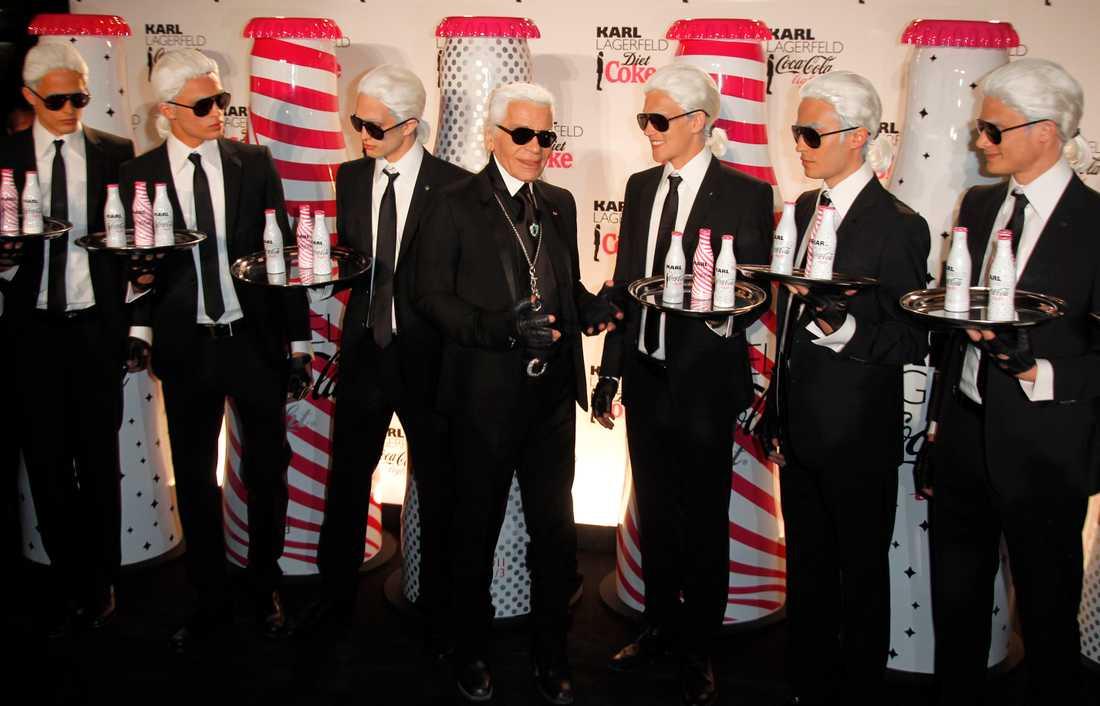 Karl Lagerfeld poserar med servitörer klädda som honom under ett evenemang med Coca Cola-flaskor som han designat. 2011