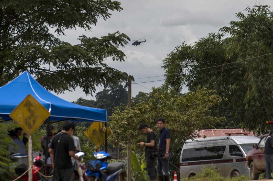 En militärhelikopter flyger över Tham Luang-grottan under räddningsarbetet.