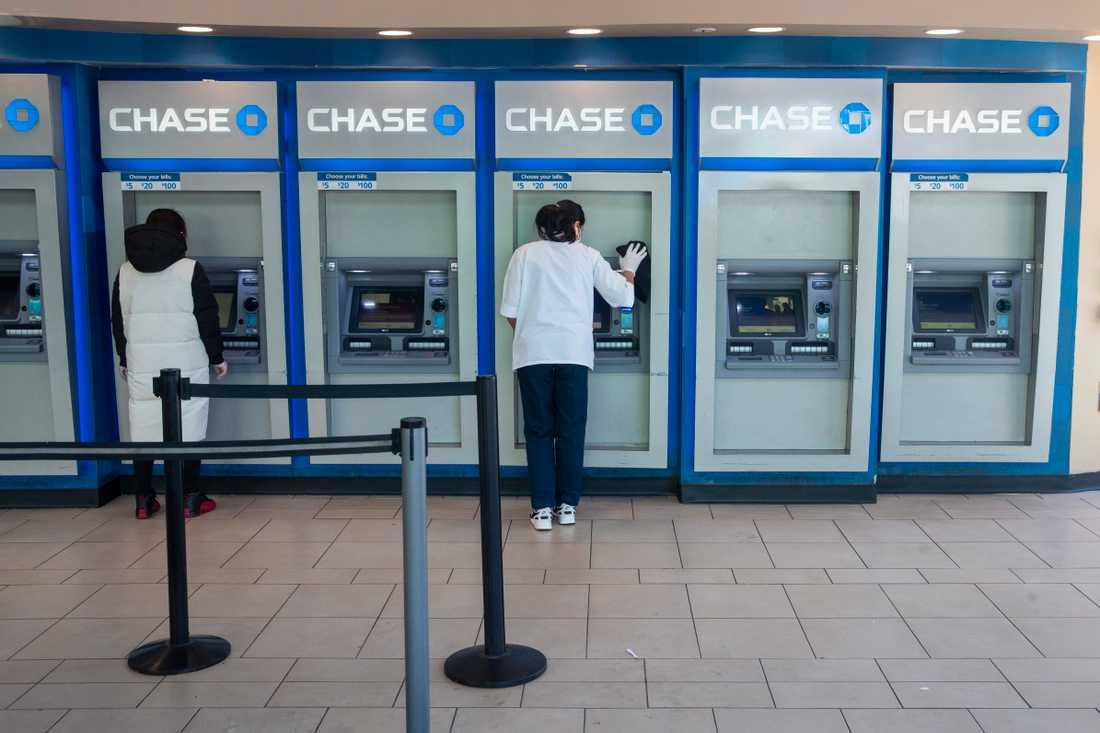 En bankanställd desinficerar bankomater i Queens.