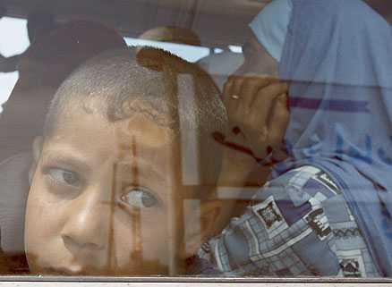 PÅ FLYKT En palestinsk pojke tittar ut genom fönstret i bussen som ska ta honom från flyktinglägret i Nahr al-Bared till säkerheten   någonstans.