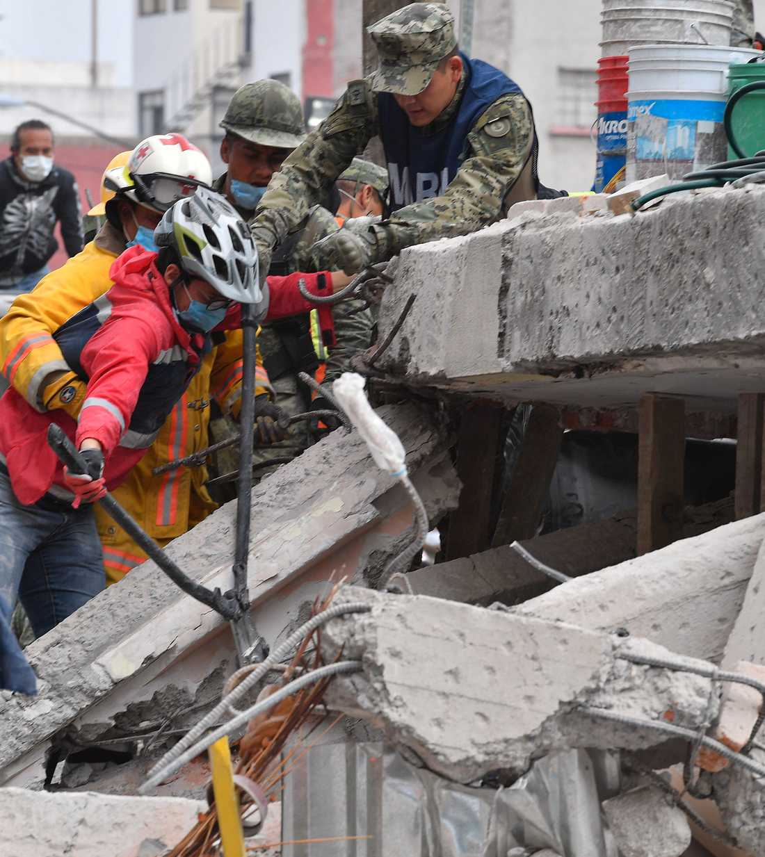 Flera byggnader har rasat samman i Mexiko City. Här arbetar räddningspersonal med att ta sig in i ett hus.
