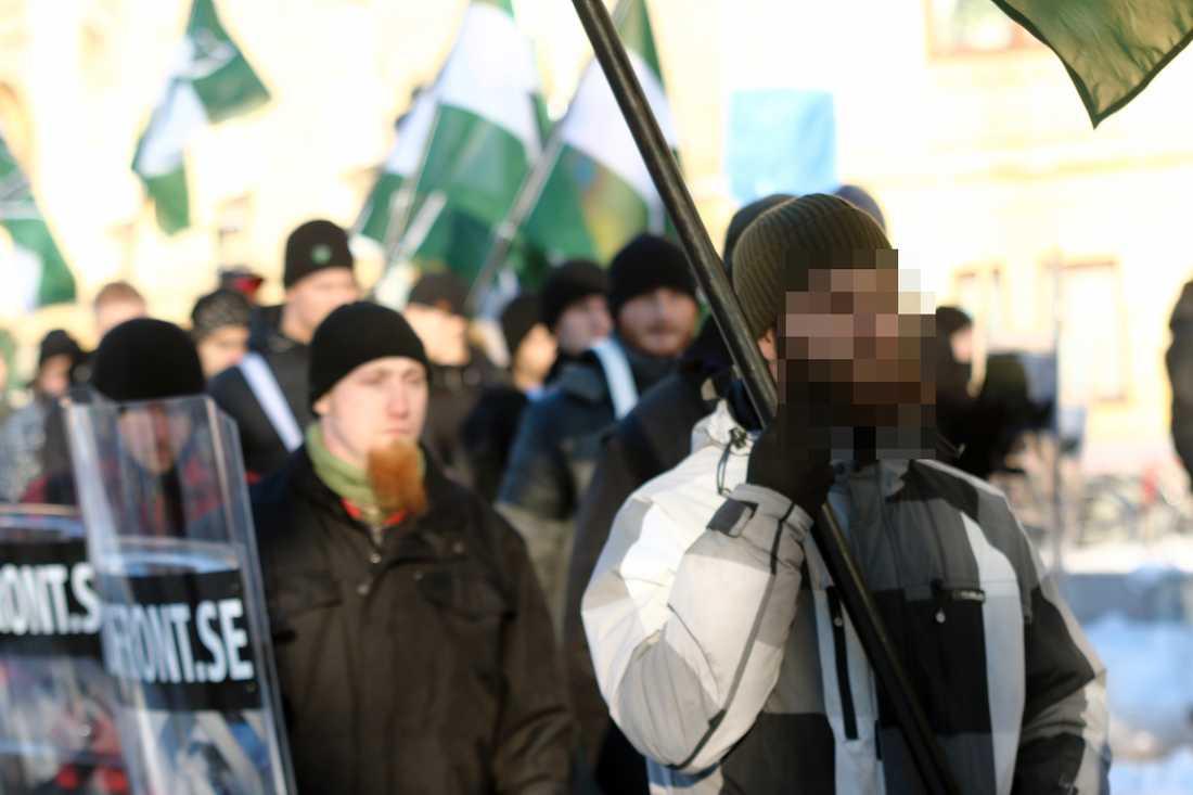 Den misstänkte 23-åringen bär flaggan. Aftonbladet har valt att inte visa ansiktet på de misstänkta bombmännen före fällande dom.