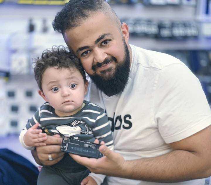 Karar Al Husseini, här med sin son, skänker munskydd till personer i riskgrupper.