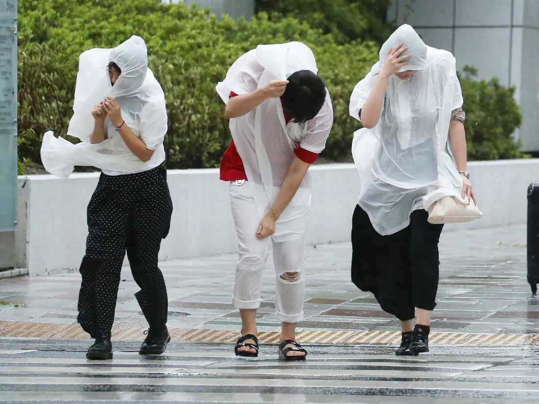 Fotgängare kämpar mot starka vindar i Nagoya.