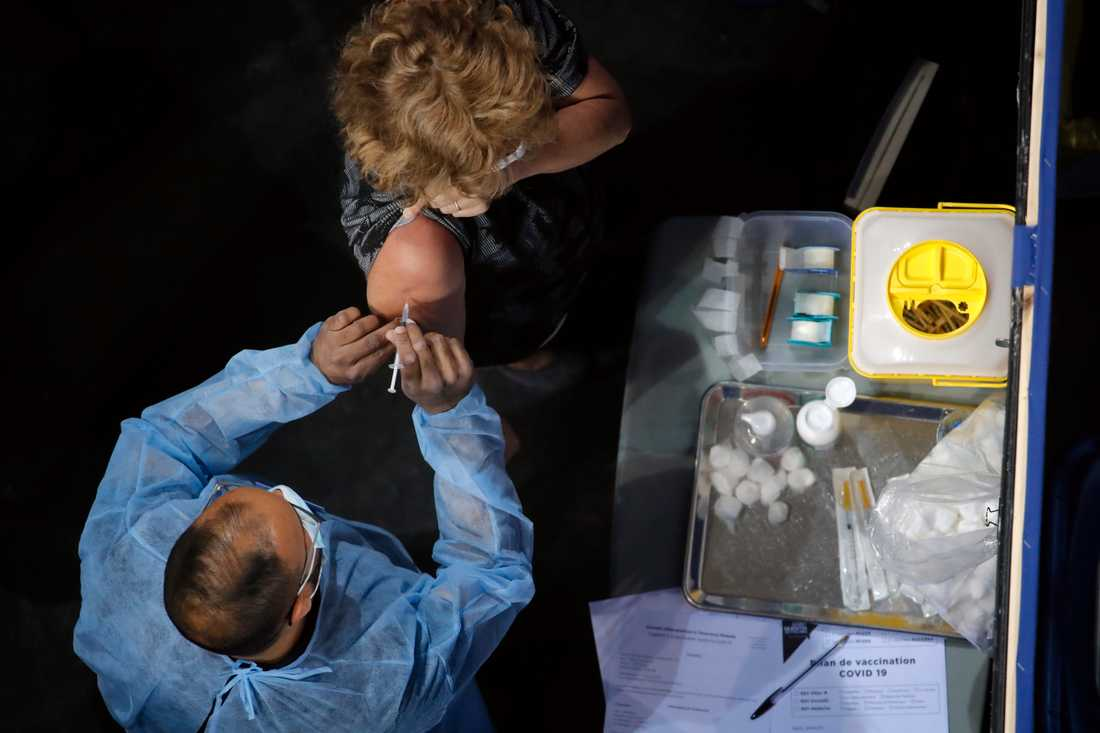 En kvinna får sin vaccinspruta på ett vaccinationscenter i Saint-Quentin-en-Yvelines, väster om Paris.