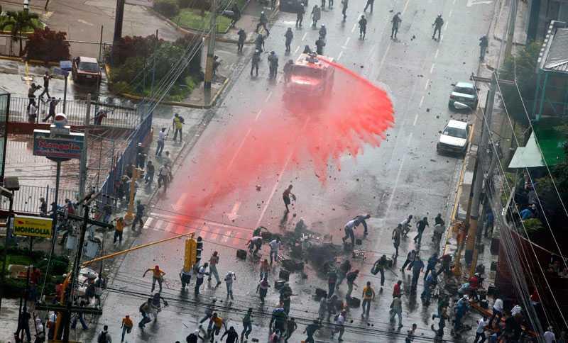 Polisen använder vattenkanoner för att skingra demonstranter utanför presidentpalatset i Honduras huvudstad Tegucigalpa på måndagen.