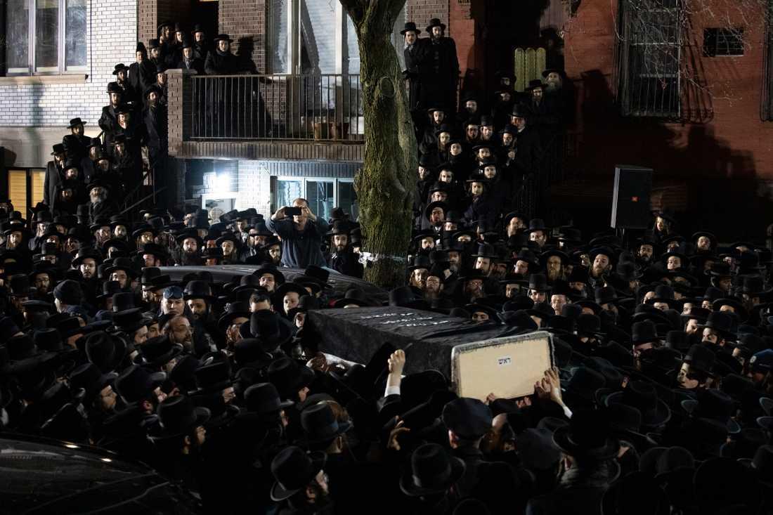 Ortodoxa judar bär fram en kista med ett av offren utanför en synagoga i Brooklyn, New York, på onsdagen.