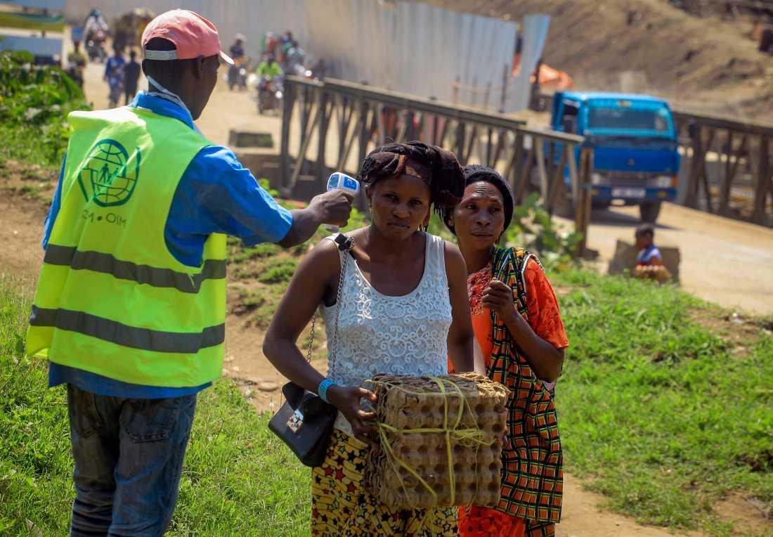 En man tar tempen på två kvinnor som korsar gränsen mellan Kongo-Kinshasa och Uganda den 12 juni 2019.