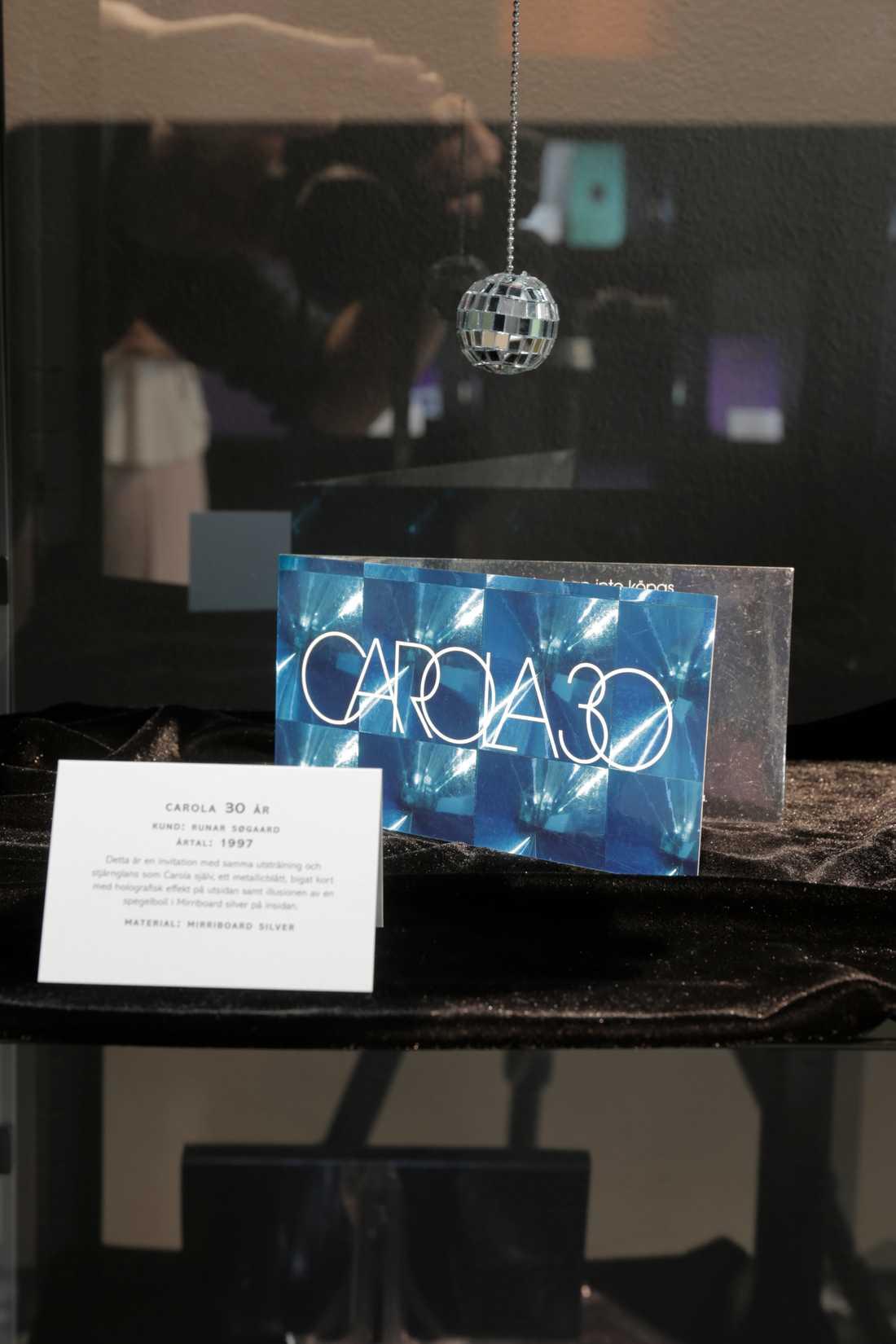 Detta är en invitation med samma utstrålning och stjärnglans som Carola själv, ett metallicblått, bigat kort med holografisk effekt på utsidan samt illusionen av en spegelboll i Mirriboard silver på insidan.
