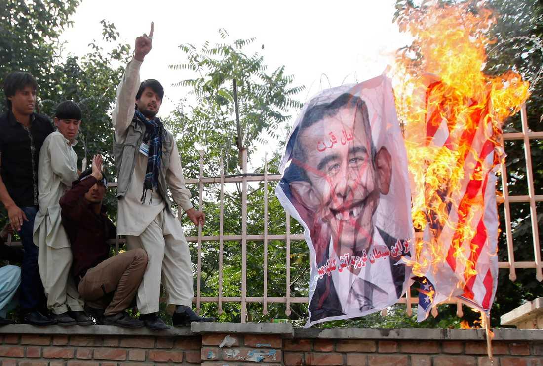 USA:s flagga – och en nidbild på Barack Obama – i lågor