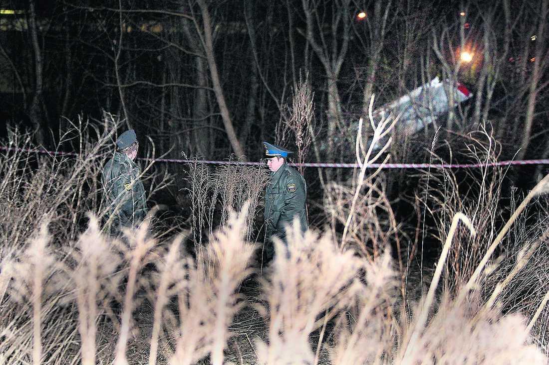 Poliser patrullerar området och lyser med sina ficklampor in över avspärrningarna.