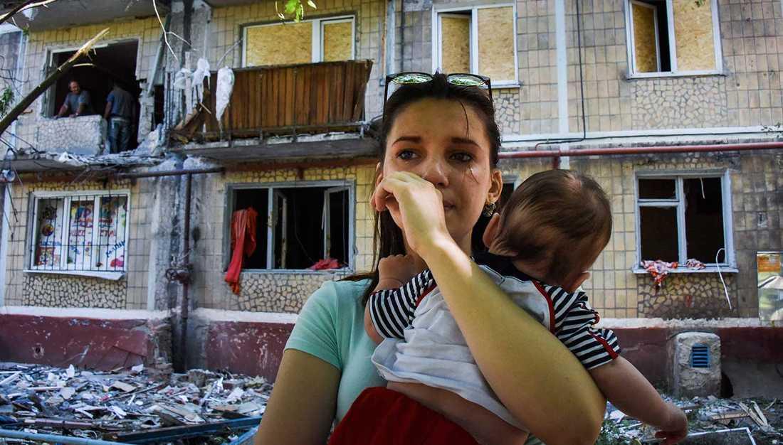 Bild från den 11 juni i år, från Horlivka i östra Ukraina. Åtminstone fyra person dödades då huset träffades av granateld. Kvinnan och hennes barn undkom fysiskt.