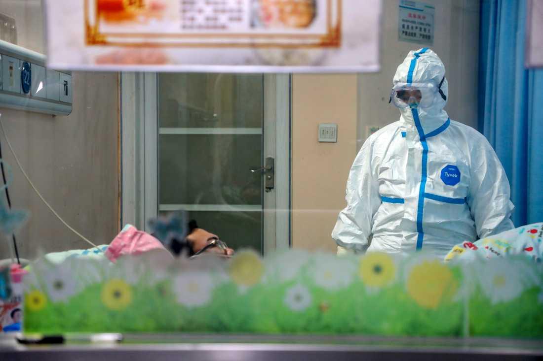 En läkare undersöker en patient i ett isoleringsrum ett sjukhus i Wuhan.