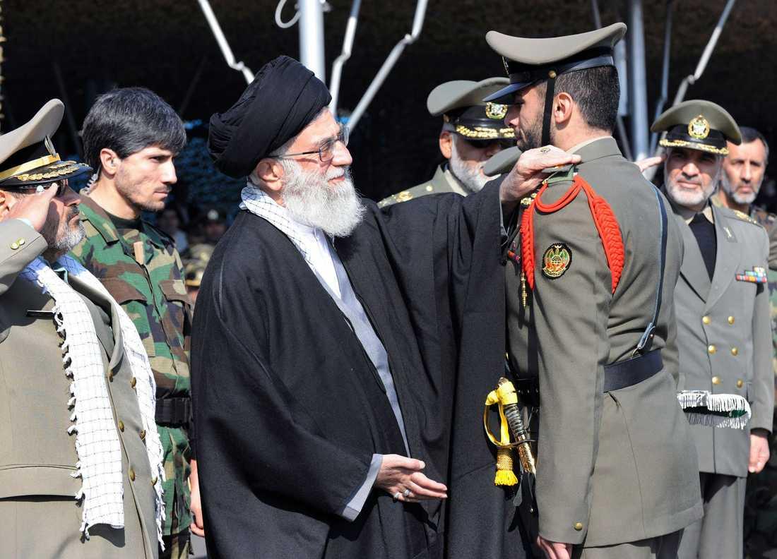 Irans andlige ledare ayatolla Ali Khamenei dekorerar en militär ur Irans armé.