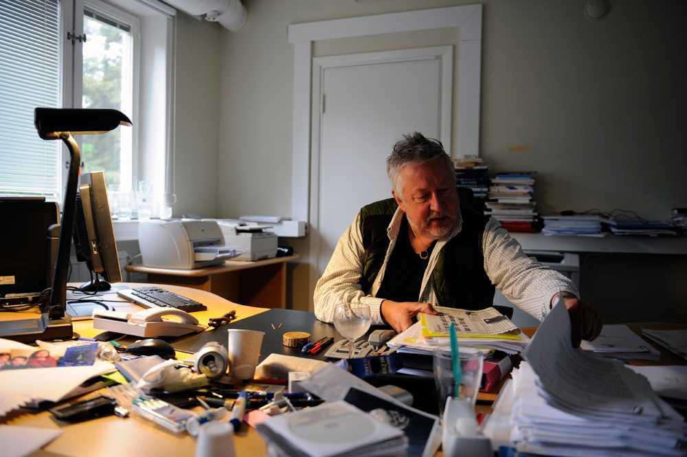 Leif GW Persson, polislegend och professor, sitter vid ett ganska stökigt skrivbord när han jobbar.