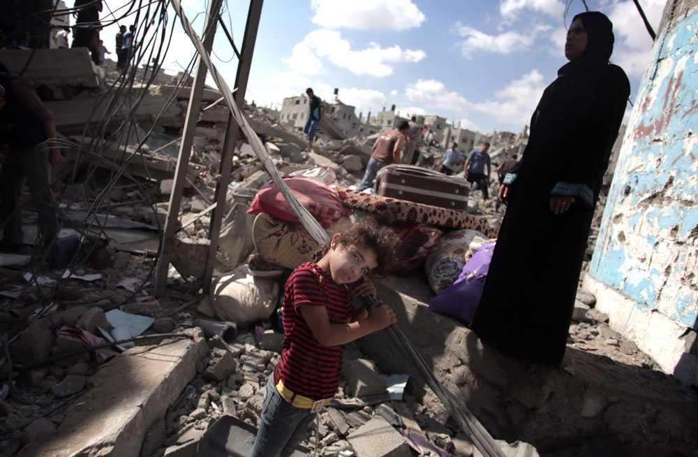 En palestinsk flicka mitt i förödelsen vid familjens totalförstörda hus.