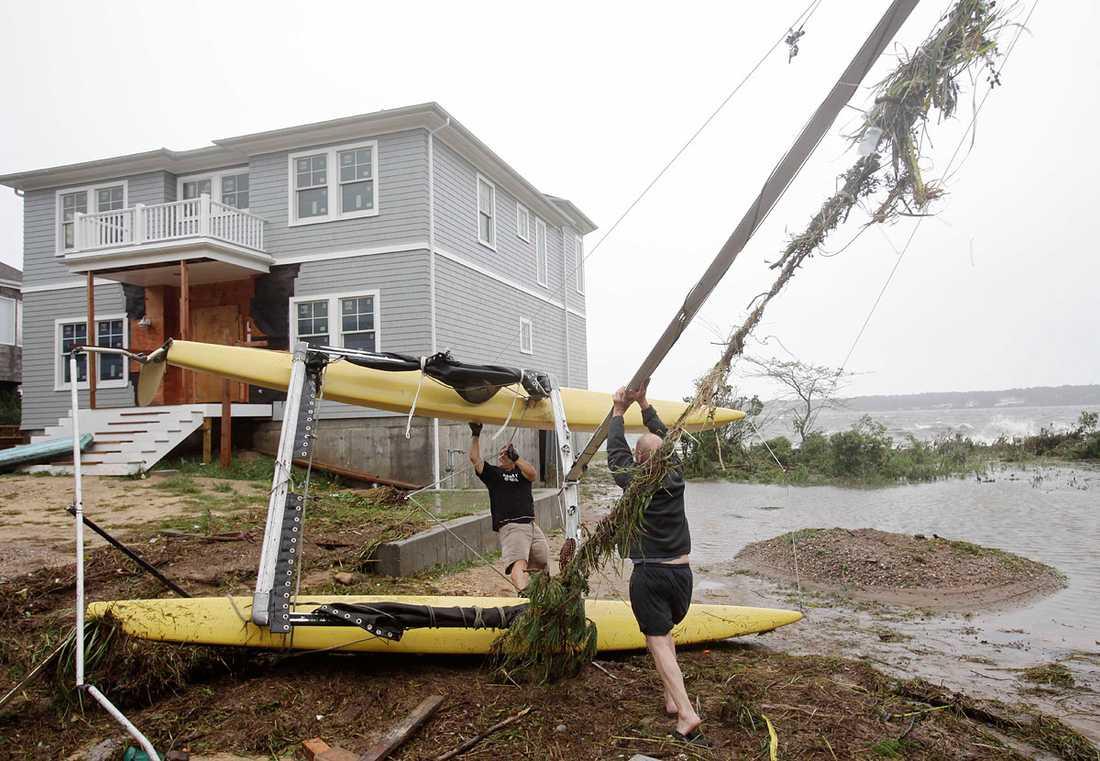 Hampton Bays, New York: En segelbåt har kastats upp på land av orkanen och lyfts på rätt köl av två män.