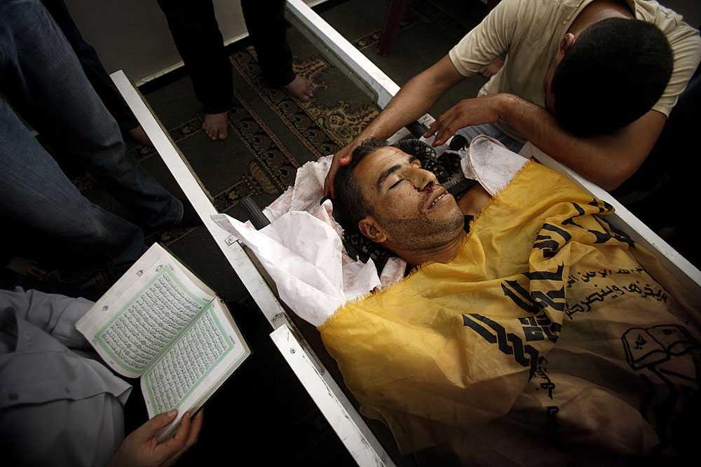 FAMILJEN SÖRJER Nael Qwader förs till kvarterets moské för en ceremoni. en av hans bröder sitter bredvid och stryker Nael över håret medan hans morbror Muhammed Amada läser ur Koranen och ber Allah om frälsning. Palestinierna berättar att Nael var fiskare, att han tillsammans med några andra män vadade ut i det långgrunda vattnet för att fånga sardiner. Att han nu är en martyr. Israels historia är en annan – om dykare som skulle attackera ett krigsfartyg och därför sköts ihjäl.