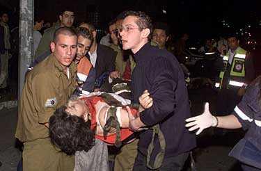 Räddningspersonal hjälper en skadad kvinna till sjukhus. De två bomberna skakade vid halvsjutiden ett område nära gamla busstationen i Tel Aviv.