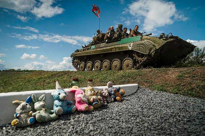 Ryssland-lojala separatister kör förbi en minnesplats för offren i MH17-katastrofen i östra Ukraina den 16 juli.