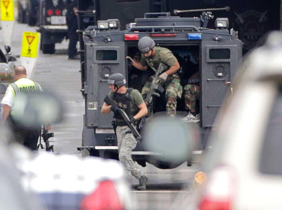 Tungt beväpnad polis rusar ut från en bepansad bil.