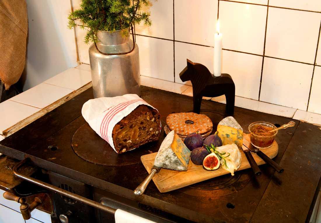 UPPDUKAT. På vedspisen i köket välkomnas gäster med en bricka med ostar från trakten, färska fikon, fikonmarmelad, knäckebröd och ett hembakt bröd med frukt och nötter.