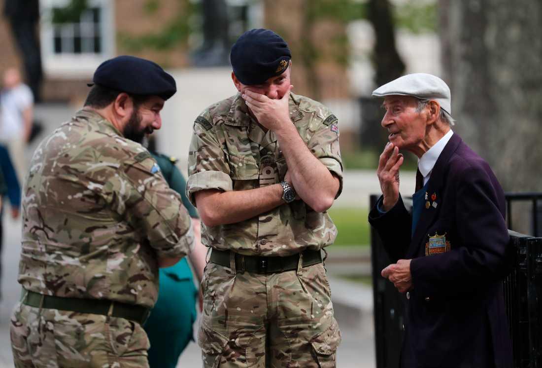 En krigsveteran (till höger) talar med yngre kollegor, efter två minuters tystnad på Whitehall i London.