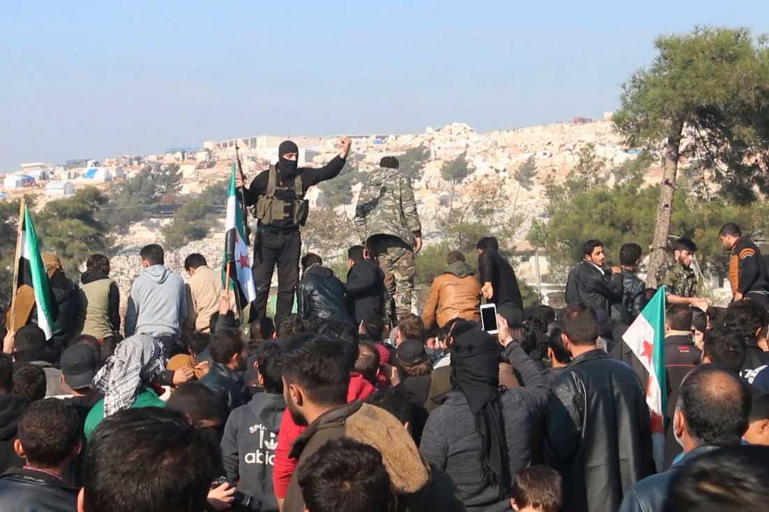 Stridande från jihadistalliansen Hayat Tahrir al-Sham försöker skingra en folkmassa som protesterar mot regeringssidans flyganfall i Idlib. Arkivbild från den 20 december.