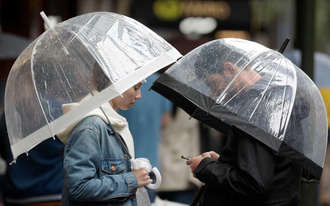 Ett par tar skydd under paraplyer från regnet över Sydney på fredagen.