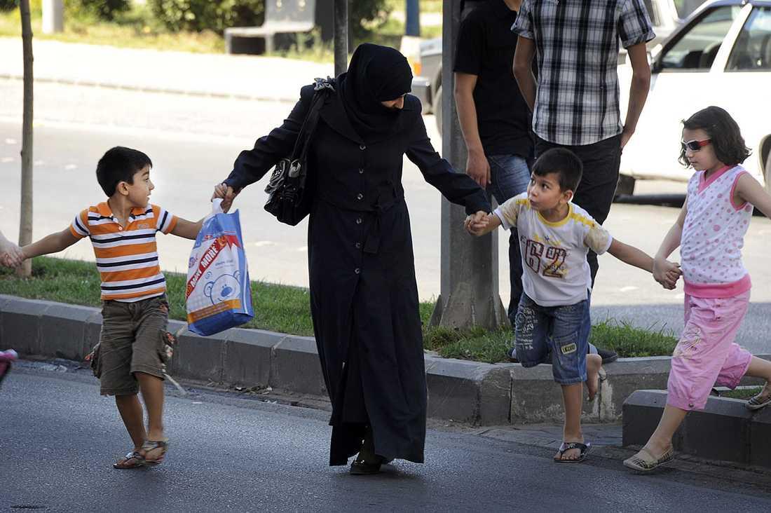 En kvinna med barn i staden Homs i Syrien. De som kan ger sig ut på stan på dagen istället för på kvällen – när det kan vara farligt att vara ute.