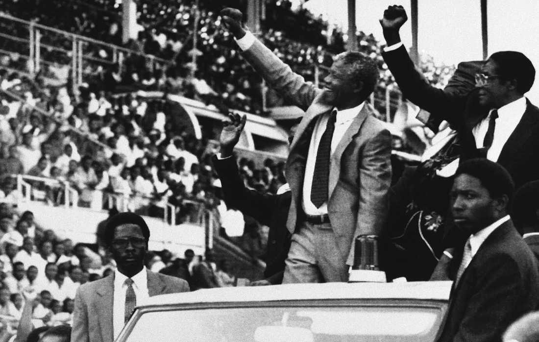 """Nelson Mandela och Robert Mugabe hälsar åskådarna välkomna till den nyinstiftade Zimbabwiska helgdagen """"Mandela day"""" i Harare, Zimbabwe, 1990. Mugabe tvingades avgå efter en militärkupp 2017."""