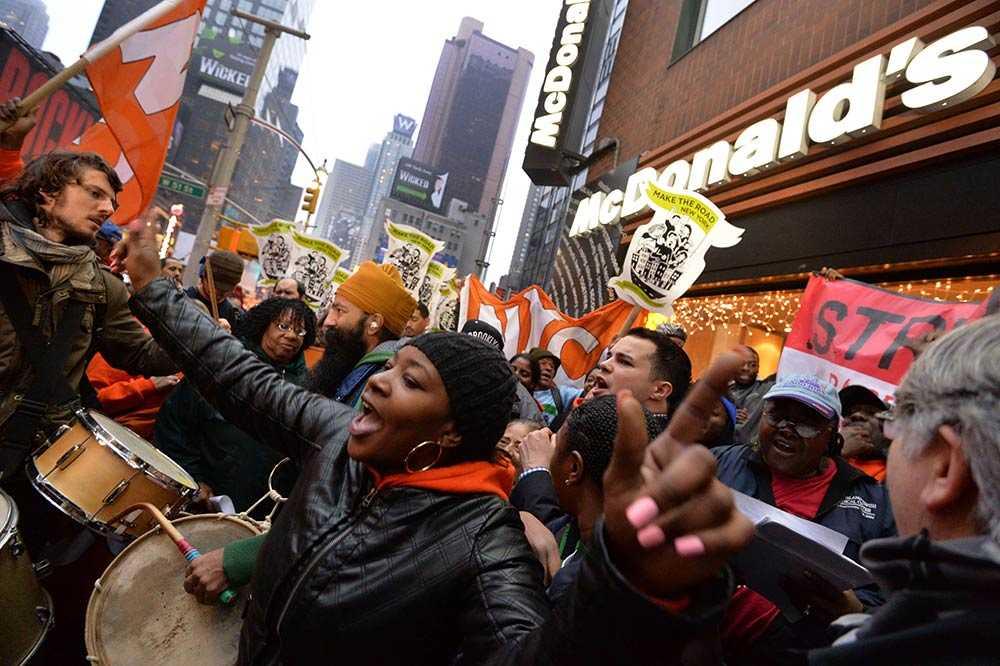 Restaurangpersonal demonstrerar mot dåliga lönevillkor utanför en McDonalds-restaurang nära Times Square i New York.