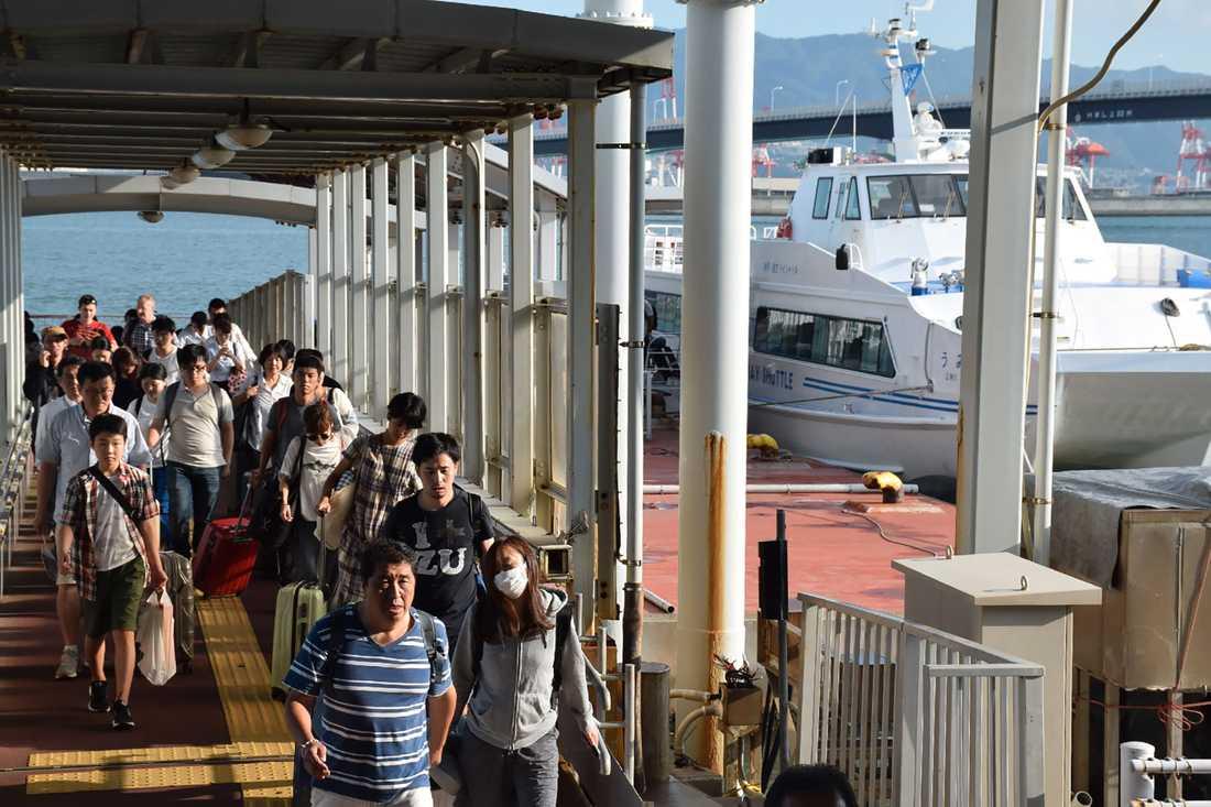 Strandade resenärer evakueras med båt från Kansai-flygplatsen.